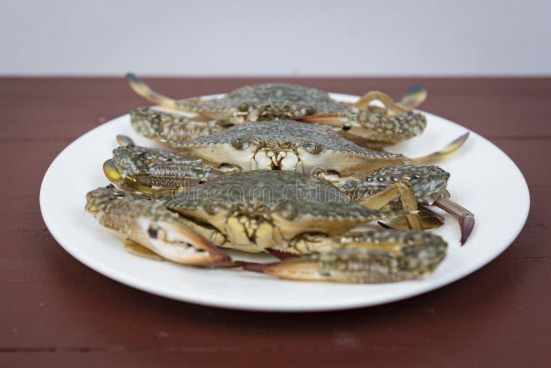 Blauwe krabben op plaat, op een houten achtergrond stock foto's