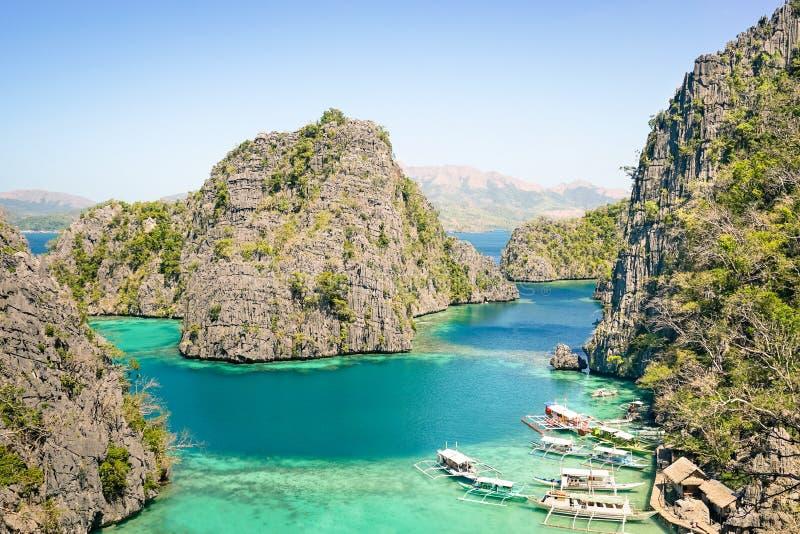 Blauwe lagune met longtailboot door Karangan Lake in Coron Palawan royalty-vrije stock fotografie