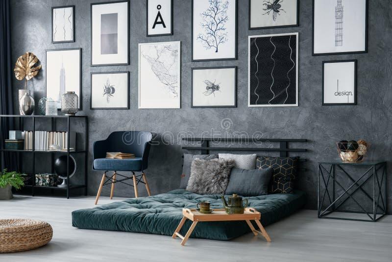 Blauwe leunstoel naast groene futon in slaapkamerbinnenland met poef en galerij van affiches Echte foto stock foto