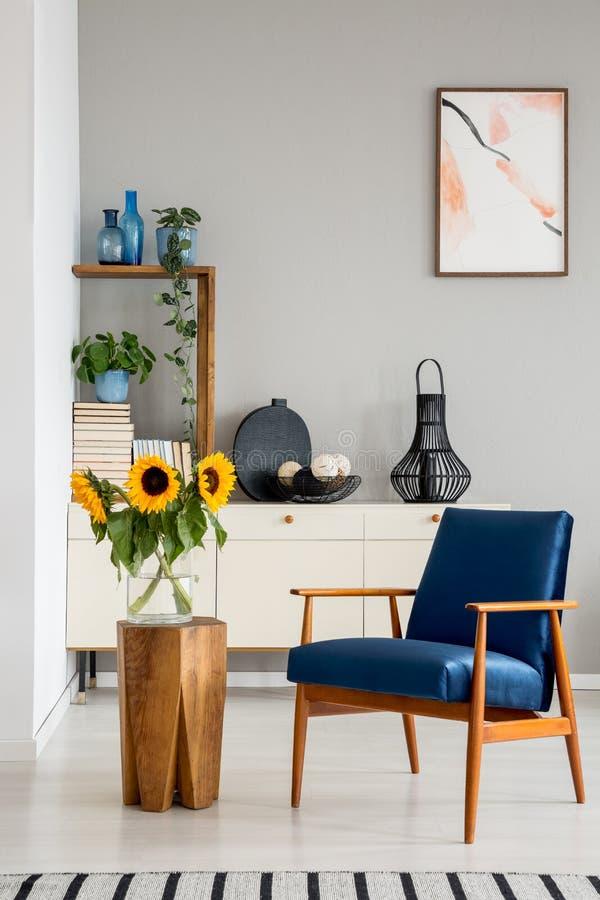 Blauwe leunstoel naast houten lijst met zonnebloemen in grijs vlak binnenland met affiche royalty-vrije stock fotografie