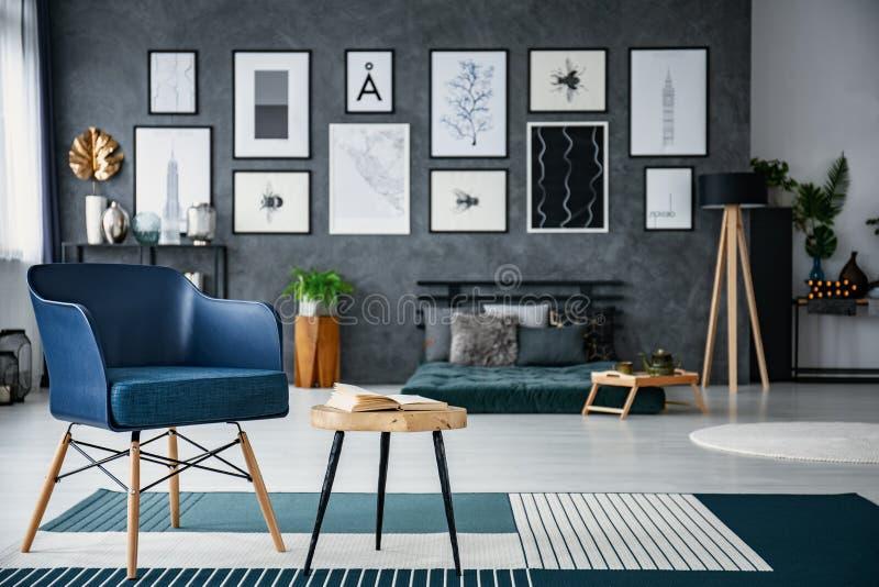 Blauwe leunstoel naast houten lijst in ruim woonkamerbinnenland met galerij en lamp Echte foto met vage achtergrond stock fotografie