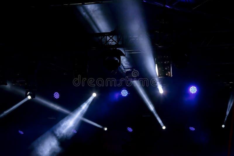 Blauwe lichten van projectoren en zoeklichten over donker stadium stock afbeelding