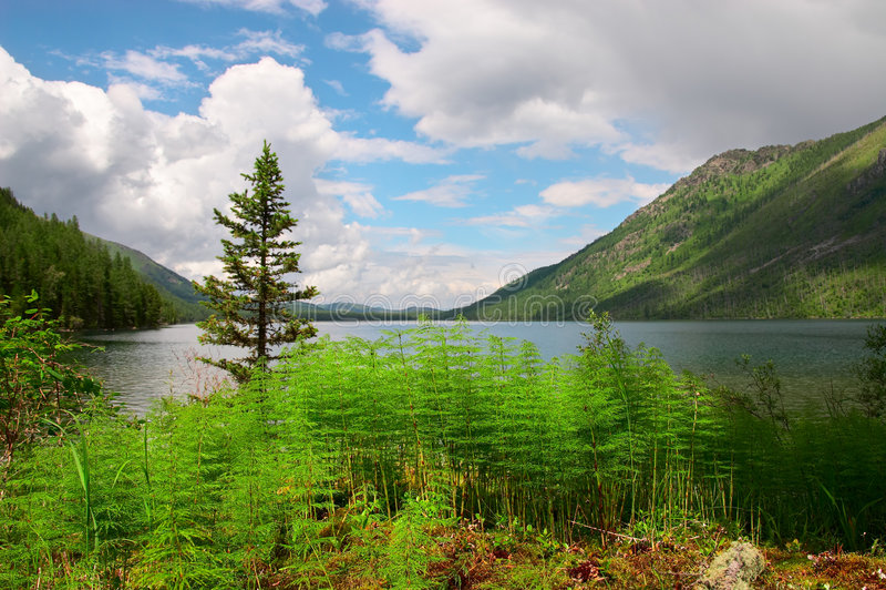 Blauwe meer, varen en bergen. stock foto