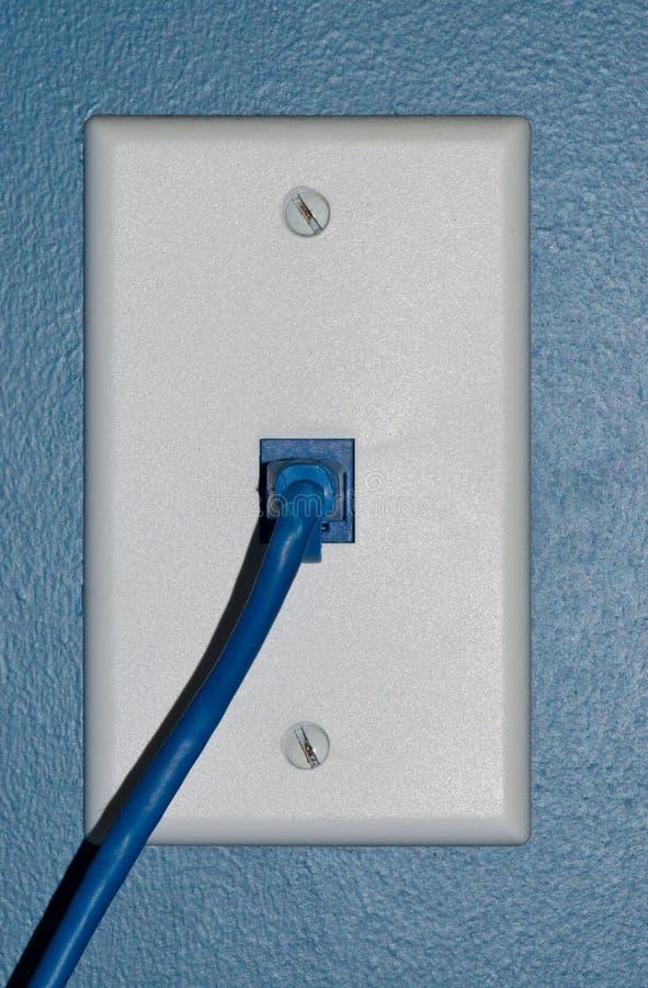 Blauwe met kabel aangesloten aan een muurafzet stock fotografie