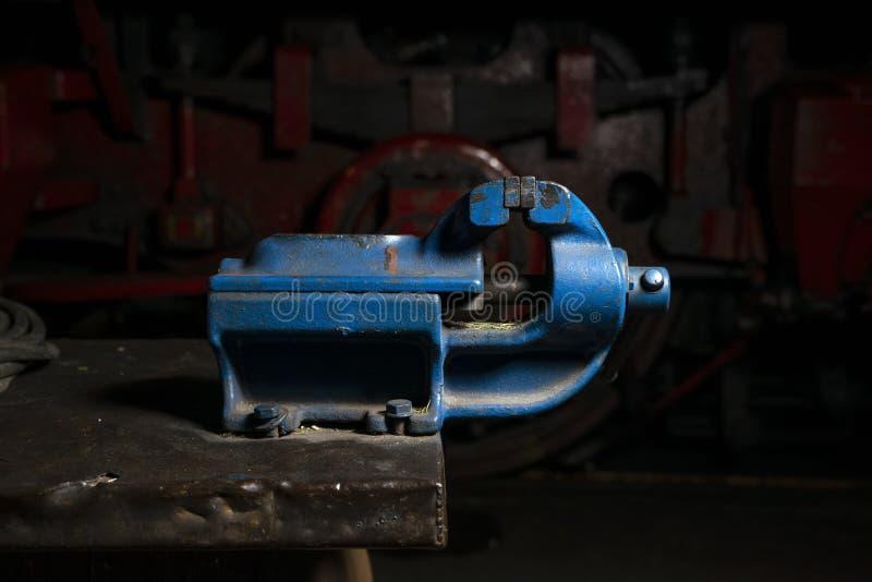 Blauwe metaal mechanische bankschroef opgezet op een werkbank in de reparatiewerkplaats stock foto