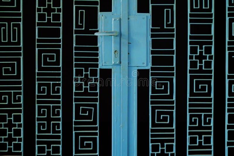 Blauwe metaalpoort op zwarte achtergrond met abstracte symbolen stock afbeelding