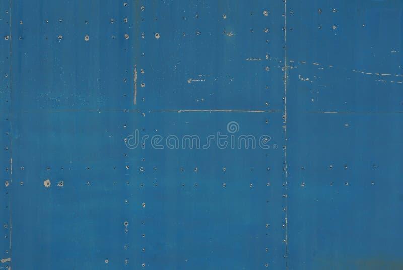 Blauwe metaaltextuur van een oude donkere sjofele ijzermuur met een naad stock afbeelding