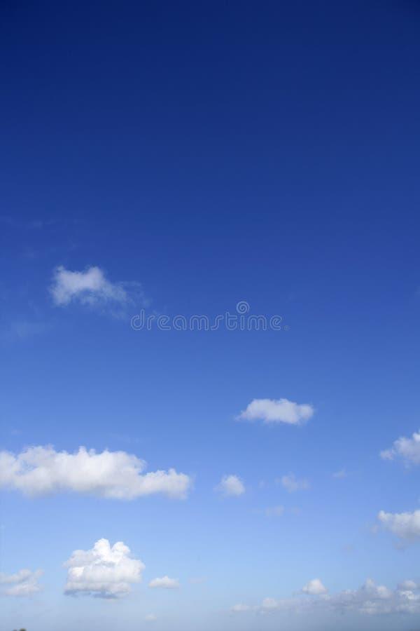 Blauwe mooie hemel met witte wolkenmening in zonnig royalty-vrije stock afbeeldingen