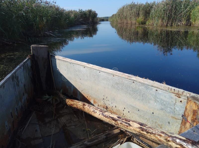 Blauwe mooie rivier en houten oude groene gele het gras natuurlijke achtergrond Rusland van de boot blauwe hemel royalty-vrije stock foto's