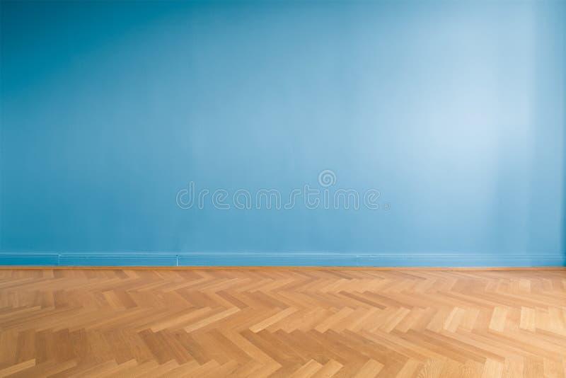 Blauwe muur in lege ruimte met parketvloer stock foto's