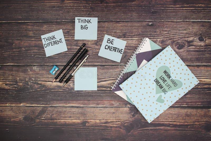 Blauwe notitieboekje en potloden en motivatienota's over het document op de lijst stock fotografie
