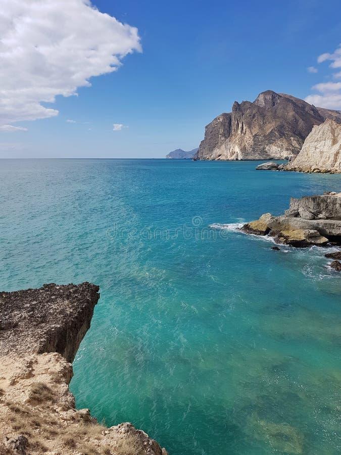 Blauwe oceaan, bergen, rotsen en verse wolken stock afbeelding