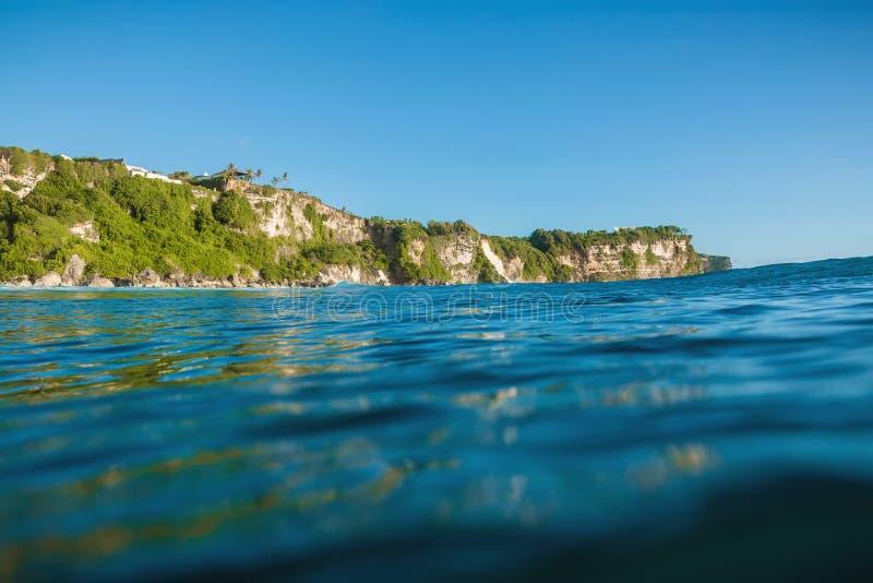 Blauwe oceaan en klip in Uluwatu, Bali en zonsonderganglicht stock fotografie