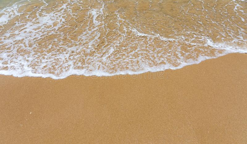 Blauwe oceaangolf op zandig strand Zachte golf van blauwe oceaan op zandig strand Achtergrond Hoogste mening van Mooi strand met  royalty-vrije stock afbeeldingen