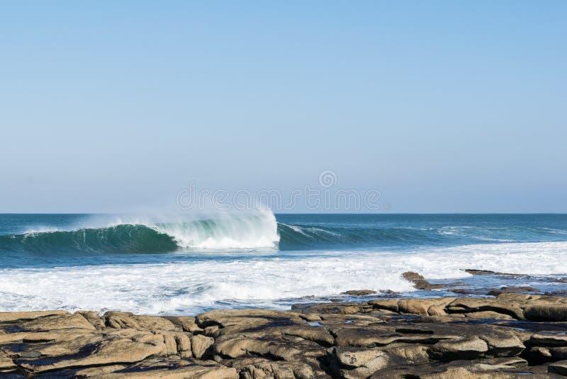 Blauwe oceaangolven die op de rotsen verpletteren stock foto's