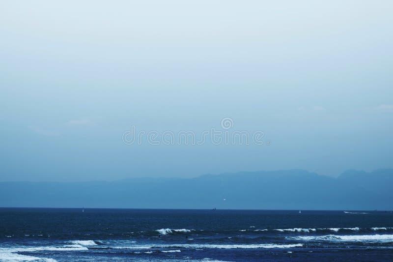 Blauwe oceaangolven en bergenachtergrond royalty-vrije stock fotografie