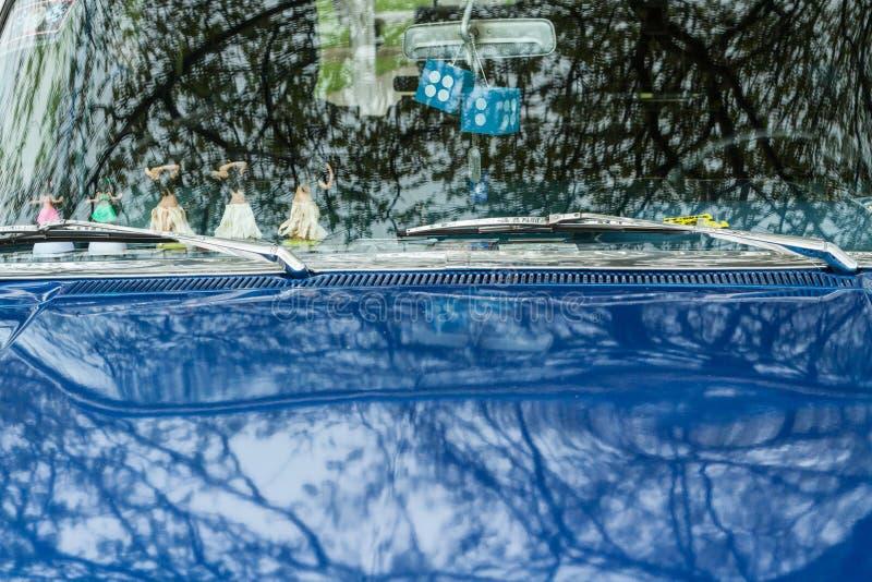 Blauwe oldtimer met bezinningen van bomen stock afbeeldingen