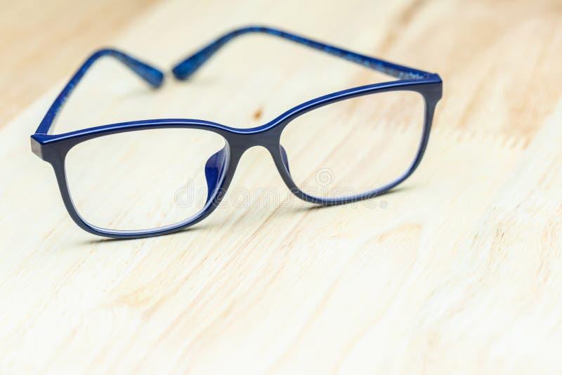 Blauwe oogglazen op houten lijst voor zaken, onderwijsconceptontwerp stock fotografie