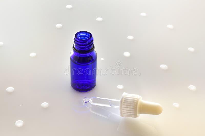 Blauwe open glaskruik en druppelbuisje op witte opgeheven lijst stock fotografie