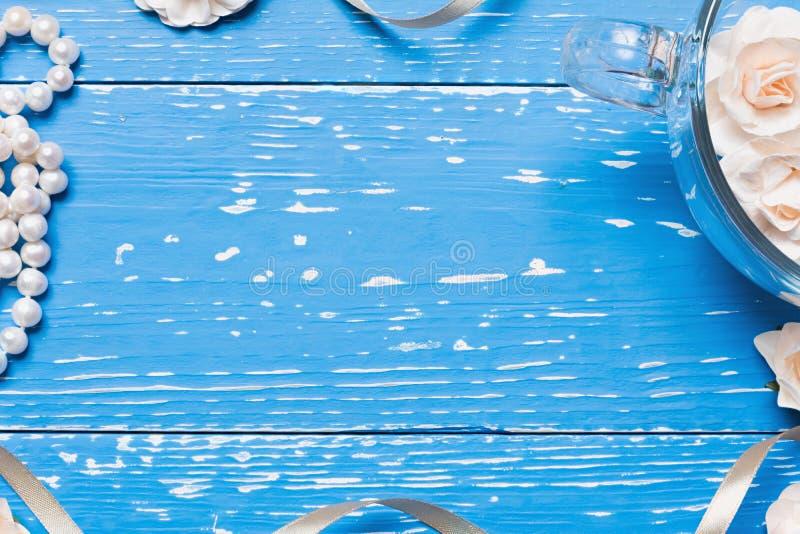 Blauwe oude houten lijst met het hoogtepunt van de glaskop van rozen royalty-vrije stock afbeeldingen