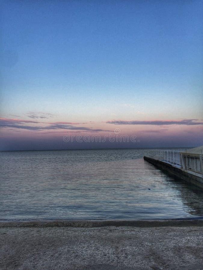blauwe overzees met een zonsondergangogenblik van roze blauwe hemel zonder wolken stock foto