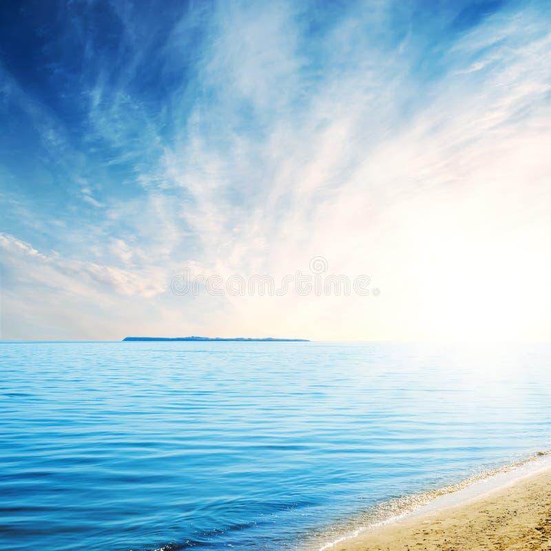 Blauwe overzees met eiland en zand onder wolken in zonsondergangtijd royalty-vrije stock foto's