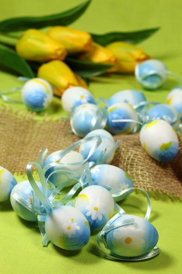 Blauwe Paaseieren en gele tulpen stock afbeeldingen