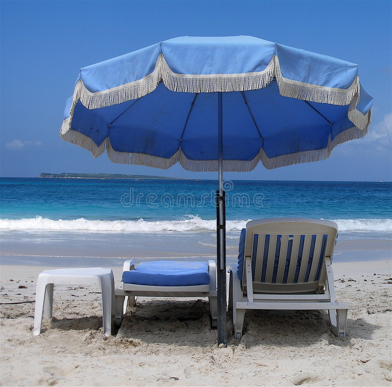 Blauwe paraplu en deckchairs stock foto's