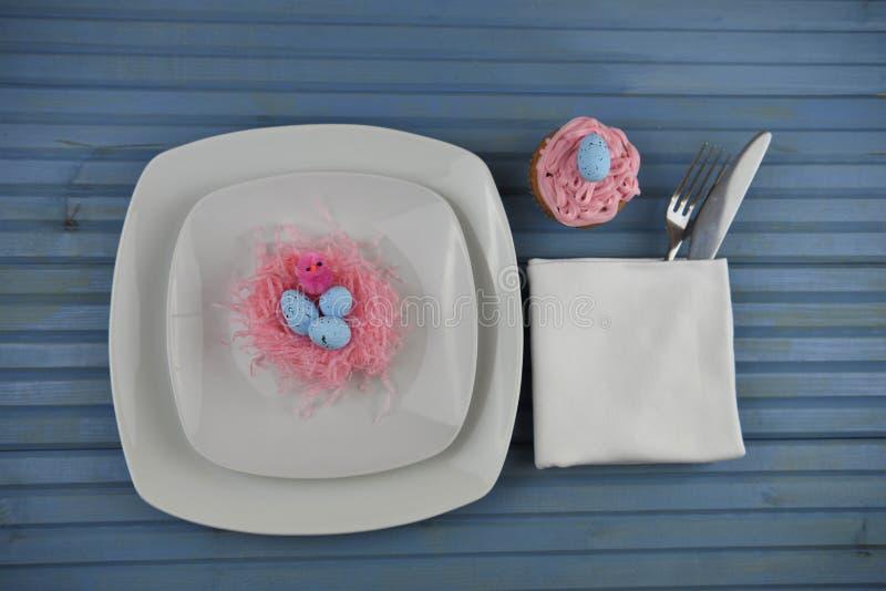 Blauwe Pasen-tijdschemaplaats die in wit plaatsen die en met een document nestpaaseieren en een roze eigengemaakte cupcake verfra royalty-vrije stock afbeelding