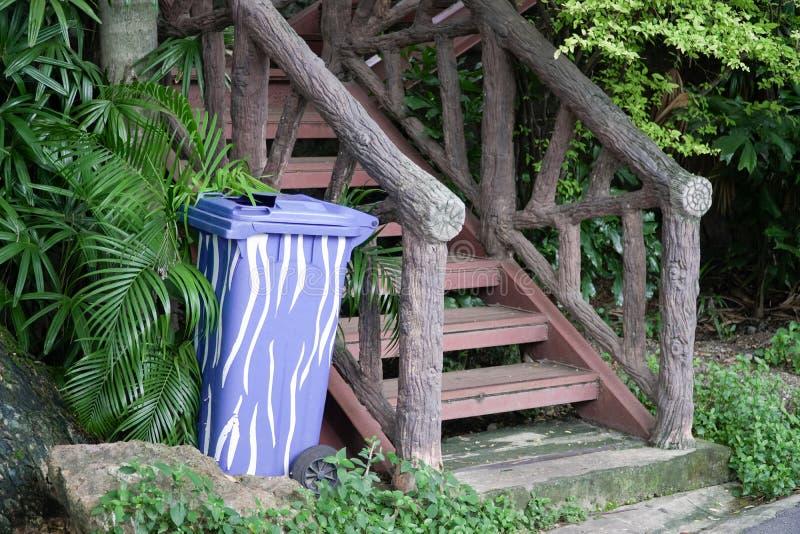 Blauwe Plastic Container of Prullenbak dichtbij Oude Treden royalty-vrije stock afbeelding