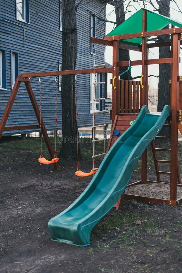 Blauwe plastic glijbaan op een houten complex spel De speelplaats van kinderen zonder iedereen stock fotografie