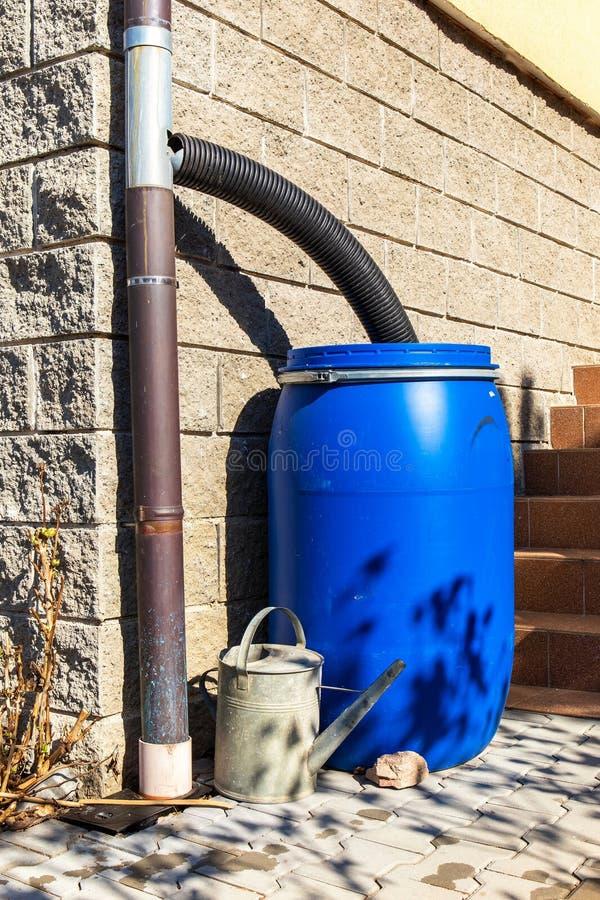 Blauwe plastic regenwatervat bewateren van de tuin Waterbesparing Watervoorziening voor droge zomer Afwatering van regenwater stock fotografie