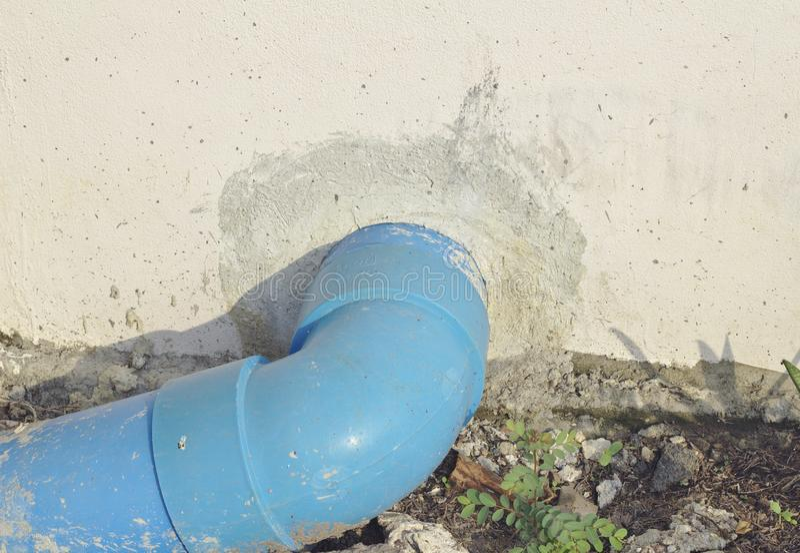 Blauwe pvc-drainagepijp buiten de concrete muur De blauwe pvc-afvoerkanalen van de drainagepijp in de grond stock foto