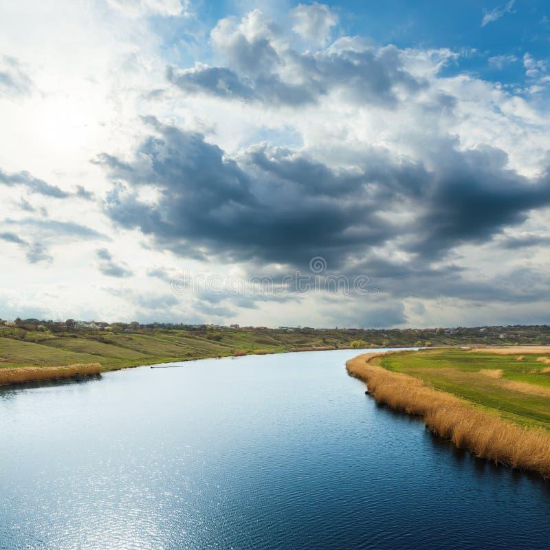 Blauwe rivier en dramatische lage wolken stock afbeeldingen
