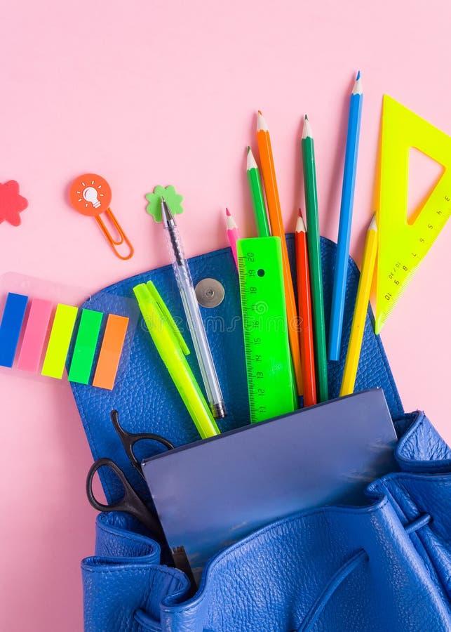 Blauwe rugzak met schoollevering op roze achtergrond stock foto
