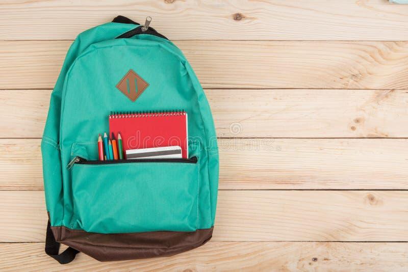 blauwe rugzak, rode notitieboekjes en potloden op houten lijst stock afbeeldingen