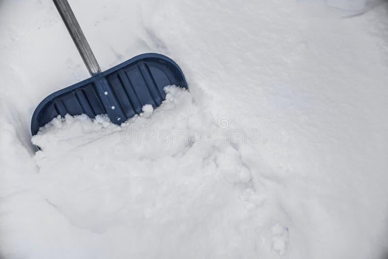 Blauwe schop in de sneeuw royalty-vrije stock afbeelding