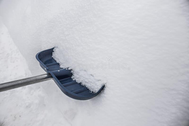 Blauwe schop in de sneeuw stock afbeelding