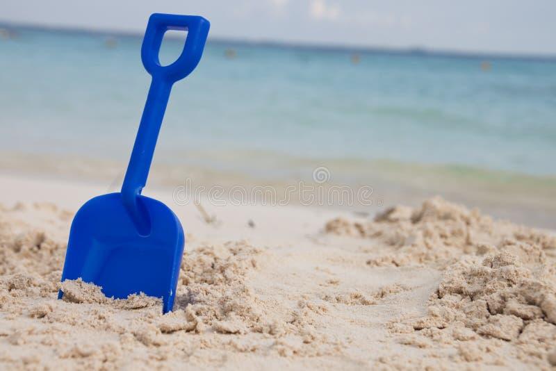 Blauwe schop in zand stock foto's