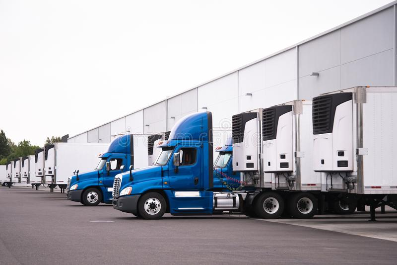 Blauwe semi vrachtwagens en semi aanhangwagenstribune in rij nauwelijks dichtbij stock foto