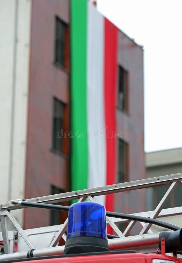 Blauwe sirene van de brandvrachtwagen en de reusachtige Italiaanse vlag stock foto