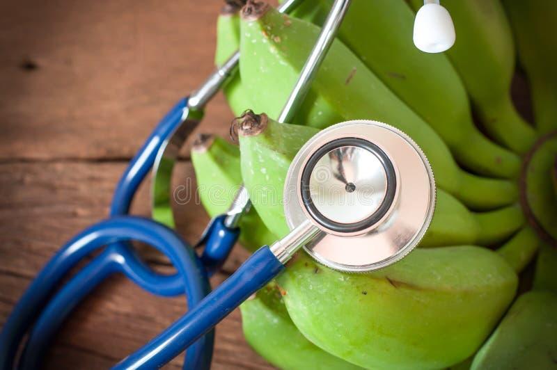 blauwe stethoscoop en groene banaan op oude houten achtergrond stock afbeeldingen