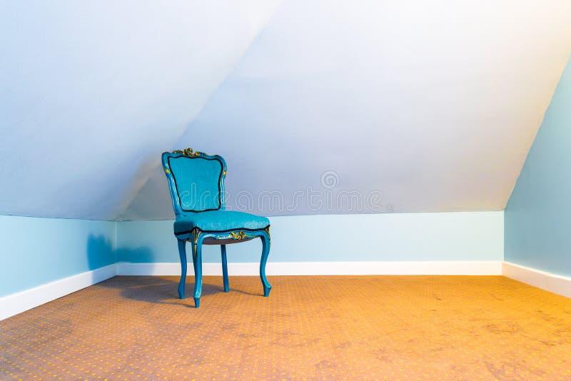 Blauwe stoel die in een lege zolderruimte, in een hoek, met wolframlicht en een bruin tapijt met vlekkenpatroon wordt geïsoleerd royalty-vrije stock fotografie