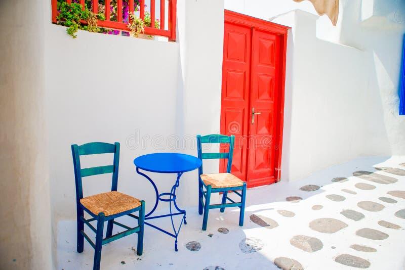 Blauwe stoelen en lijst aangaande straat van typisch Grieks traditioneel dorp met witte huizen op Mykonos-Eiland, Griekenland, Eu stock foto's