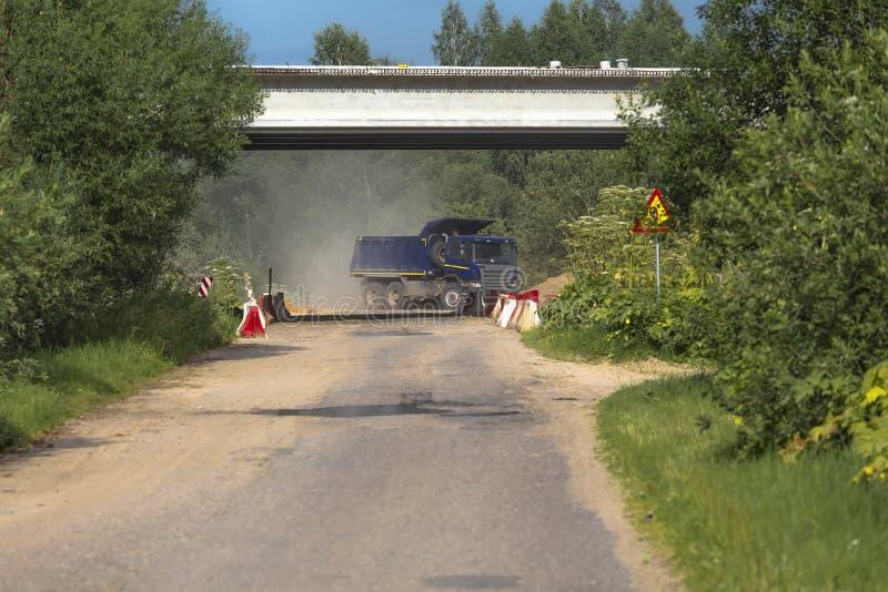 Blauwe stortplaatsvrachtwagen tegen een achtergrond van bomen stock foto