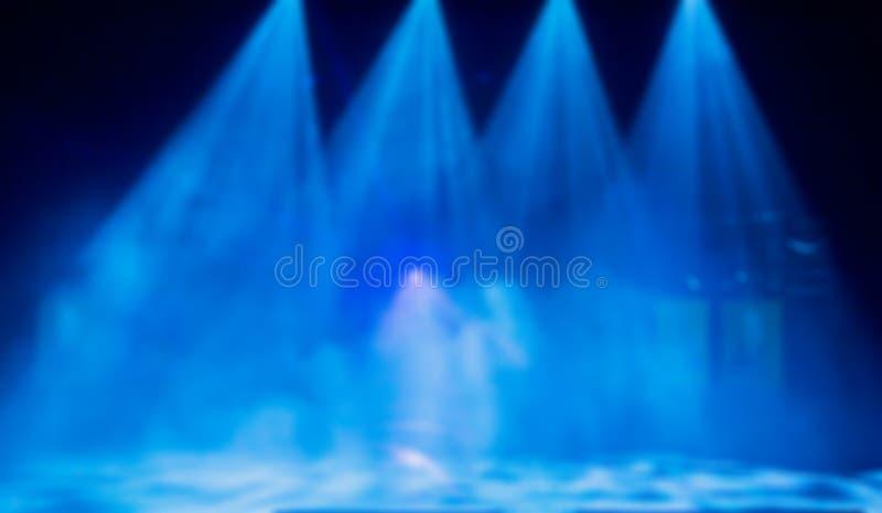 Blauwe stralen van licht van de schijnwerpers door de rook op het stadium Theatrale prestaties Defocused abstract beeld royalty-vrije stock foto's
