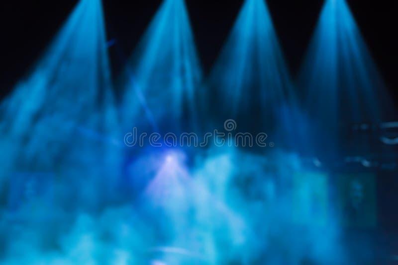 Blauwe stralen van licht van de schijnwerpers door de rook op het stadium Theatrale prestaties Defocused abstract beeld stock foto
