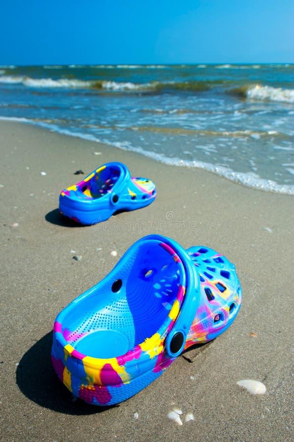 Blauwe strandpantoffels op zandig strand stock afbeelding