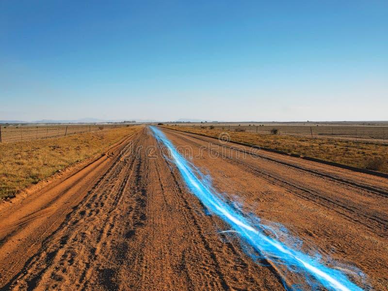 Blauwe strook van licht bij de landweg tegen duidelijke hemel royalty-vrije stock foto's