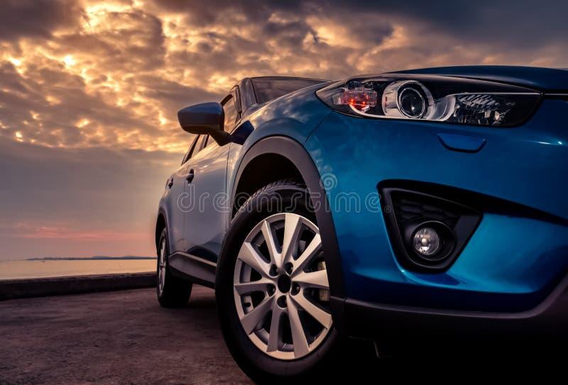Blauwe SUV-auto met sport en modern die ontwerp op betonweg door het overzees bij zonsondergang in de avond wordt geparkeerd Hybr stock afbeeldingen